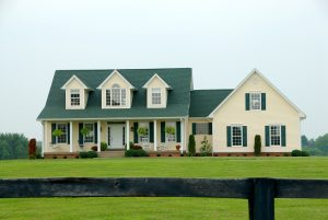 Yellow two story farmhouse with front porch and dormers